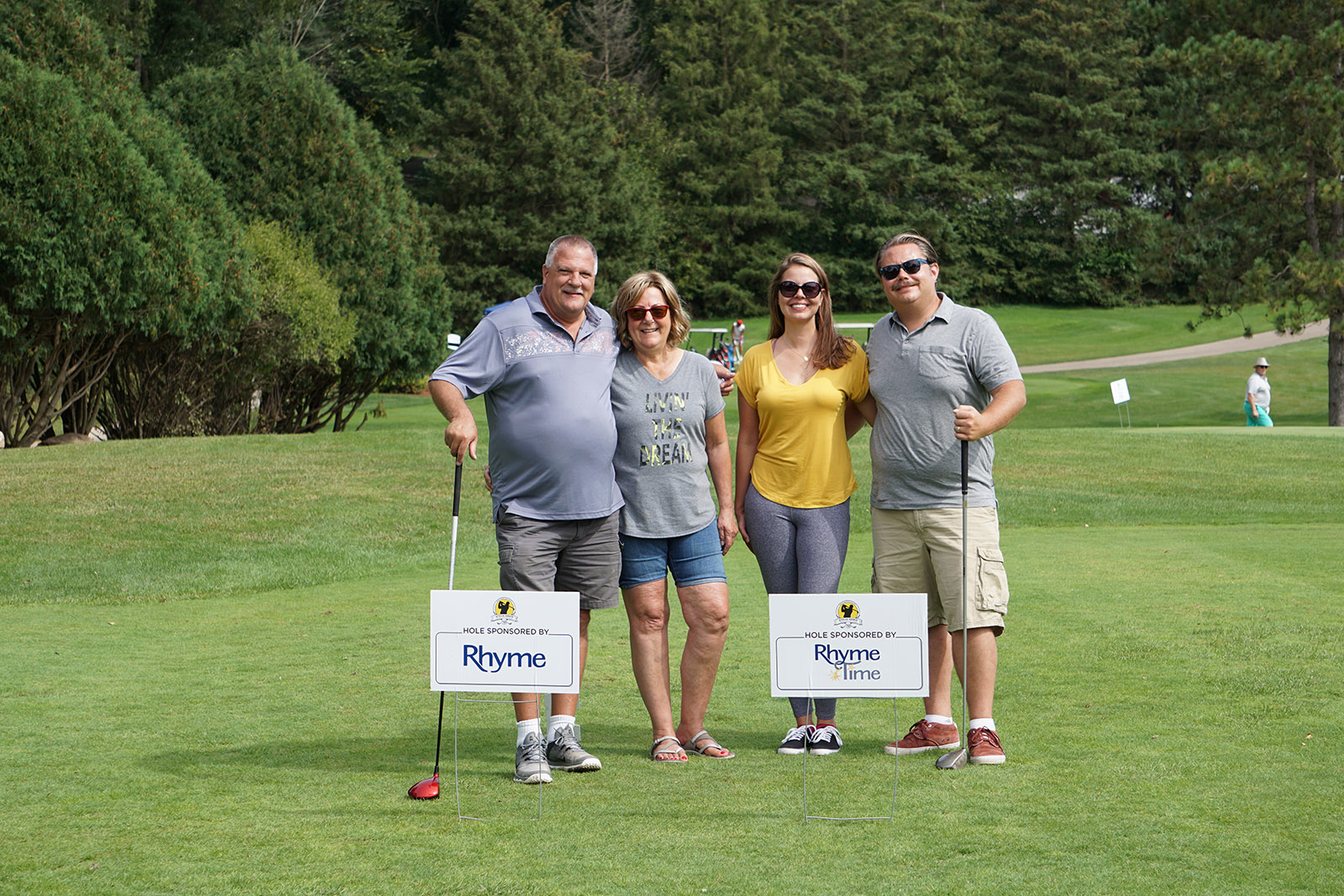 Four golfers stand next to Rhyme Time Scholarship signs at the Steve Ennis Memorial Golf Event