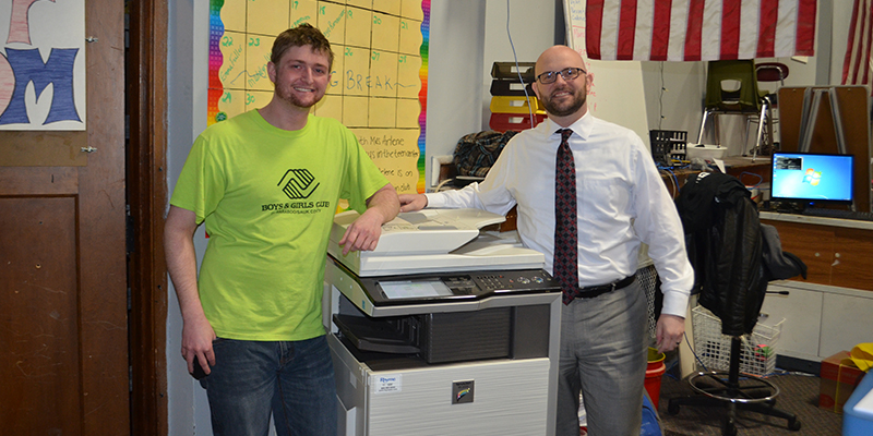 A Rhyme employee and Boys & Girls Club volunteer stand next to a copy machine donated by Rhyme