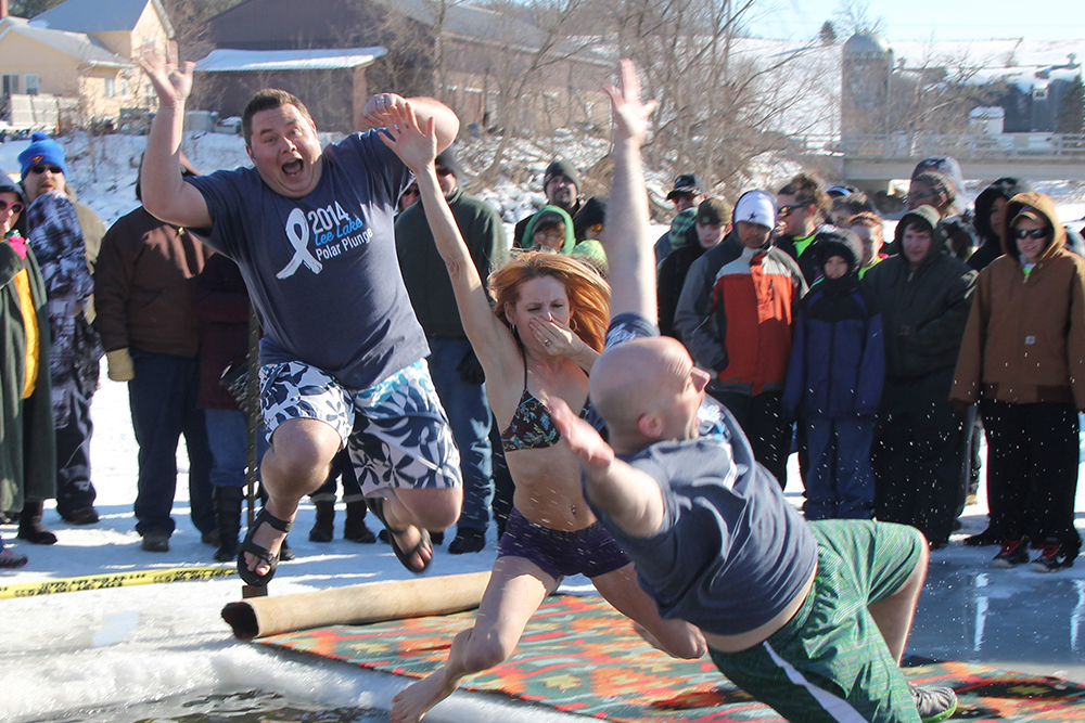 Rhyme employees leap into the water during a Polar Plunge